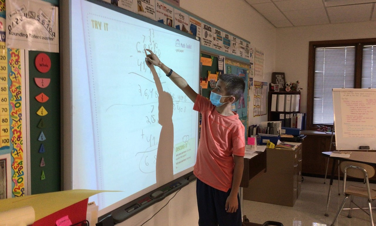 Student, boy, in Mrs. Broms' fourth grade classroom is explaining his subtraction skills to the class. He is touching the SmartBoard or electronic teaching board. He is explaining how he borrowed and added to a different column. He is wearing a blue face mask that covers his nose and mouth. He is also wearing darker colored shorts and an orange shirt.