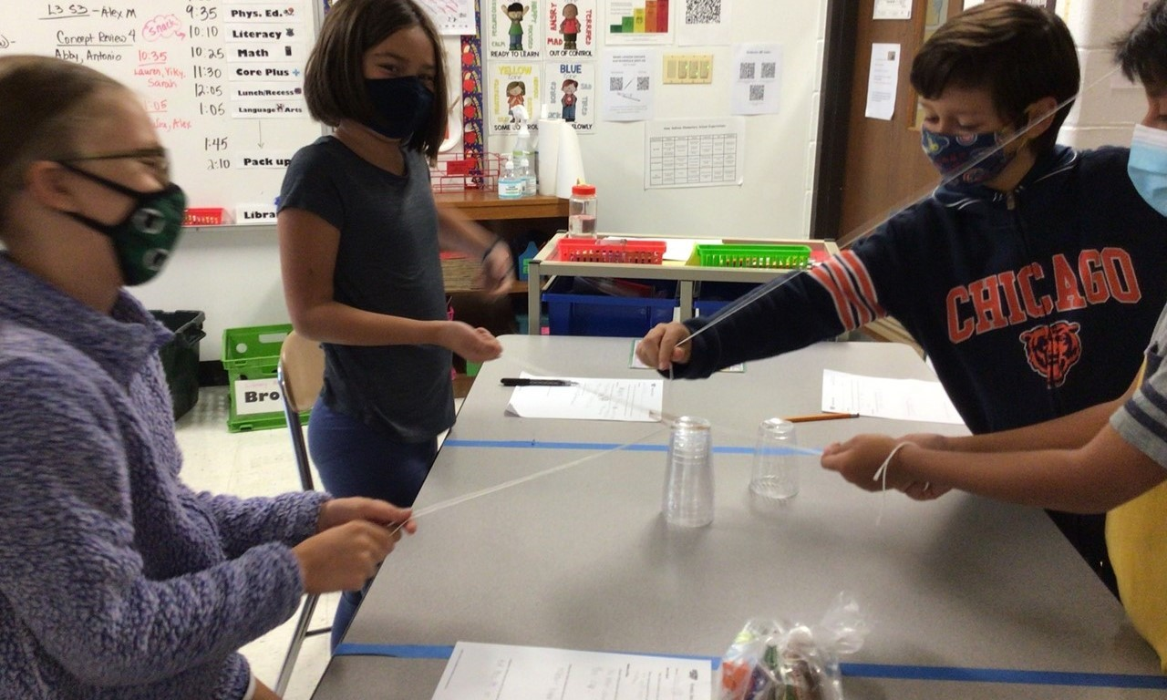 Four students hold strings that connect in the middle and they are trying to pick up a plastic waterbottle. The students, two boys and two girls, are standing next to a rectangular table with blue tape on it. Each student is wearing a mask and one student wearing a Bears football shirt is holding the string closer to the water bottle. In the background is a class schedule on the white board and graphs and charts on the wall with class information.
