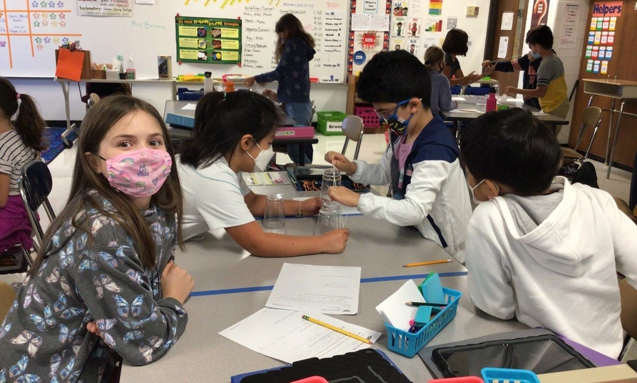 Students in Mrs. Broms' class are working on using strings to pick up a water bottle at their desk. One girl is looking into the camera. All students are wearing masks. There are four students in the foreground and five students sitting or standing in the background with their groups. There are papers, pencils and blue pencil bin filled with supplies and post-its.