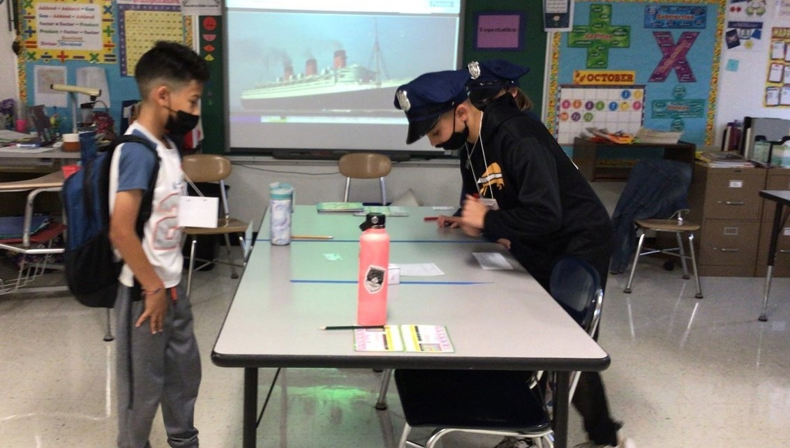 Two students dressed up as police officers are questioning another student who is leaving the room during the Ellis Island simulation at school. Students learned about immigration into the United States through Ellis Island. Students pretended to be officers, boat captains, and travelers throughout this time. There is one student standing in front of the students dressed up as officers and he is holding a piece of paper and is wearing his backpack. All students are wearing face masks.