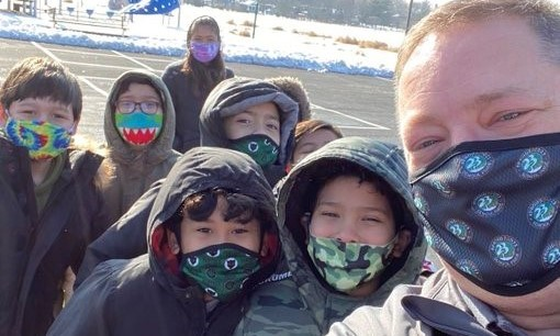 A group of kids outside with the Superintendent and their masks looking at the camera person
