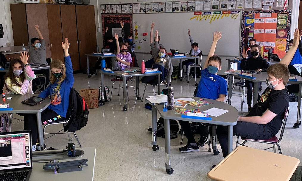 Students in Mrs. Lett's class are raising their hands while sitting at their desks in the classroom. They are wearing masks and waiting to participate in