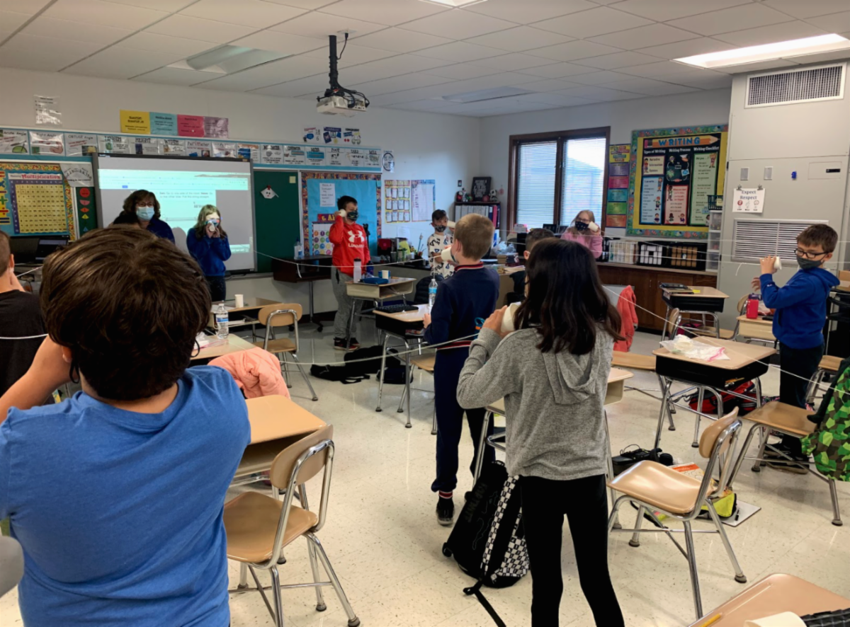 Mrs. Broms' class was learning about sound in science. The class is standing up with paper cups to their ears and strings attached to them. They created string phones and were standing far apart from their partner to hear and feel how sound travels from a distance  and sound waves.
