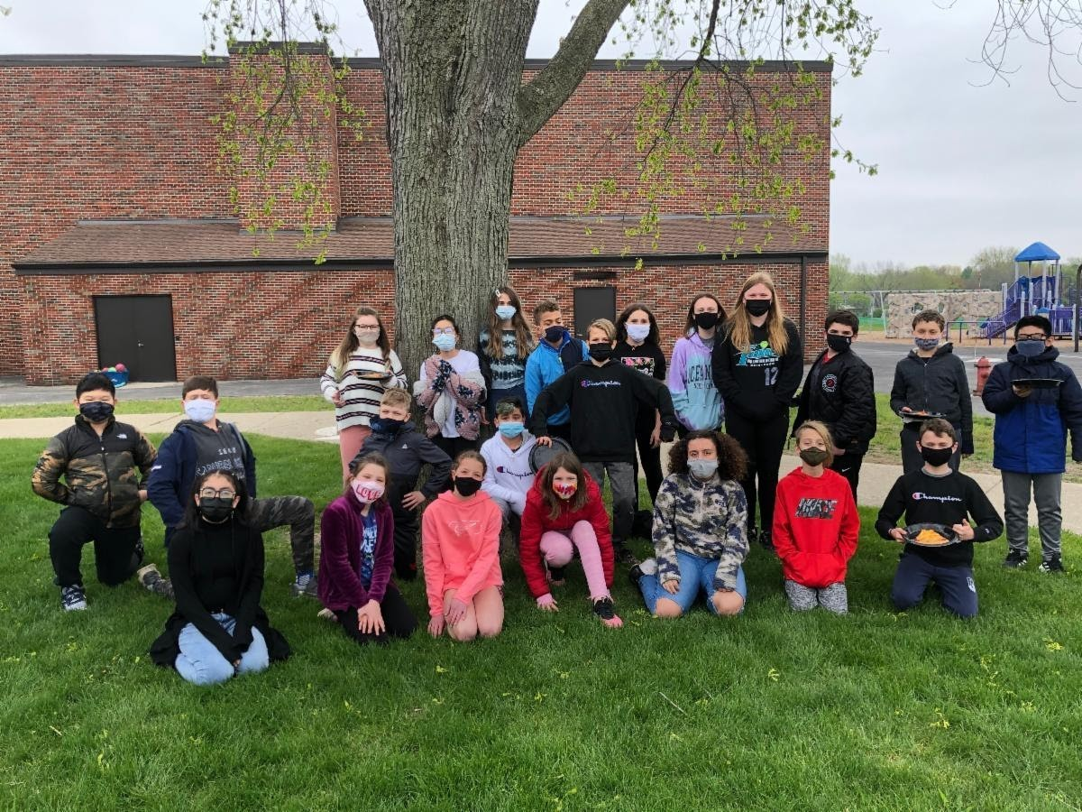 Mrs. Pennell's class is outside with posing for a picture as a class with their masks. They are celebrating their class win on solving logic puzzles and had earned a pizza party. After the party they had time for an extra recess. The students are kneeling or standing near the tree behind Anne Sullivan School. The playground is in the background and the building housing the gym is there too.