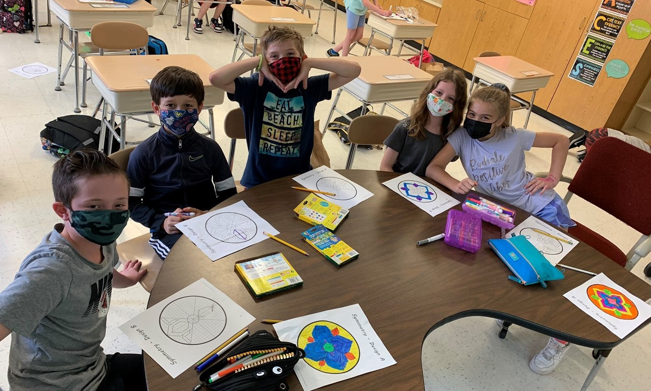 Group of students in masks working on an assignment