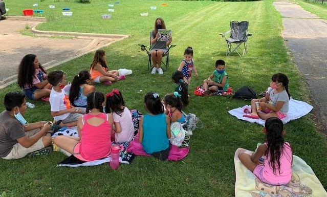 Teacher reading to kids out in the park