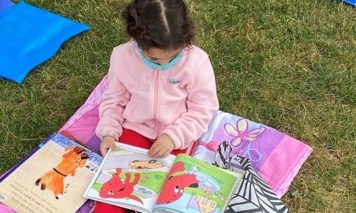Girl reading in the park on her blanket
