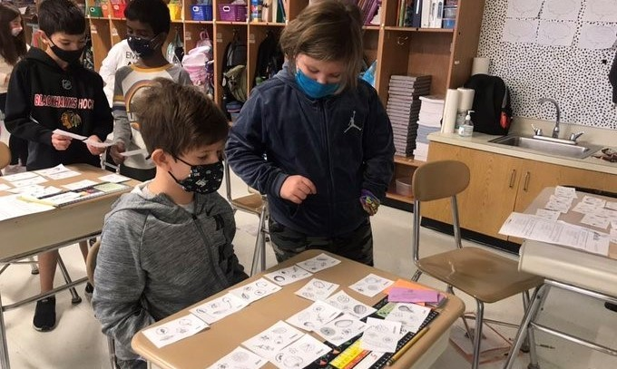 Two students sorting flashcards on a desk
