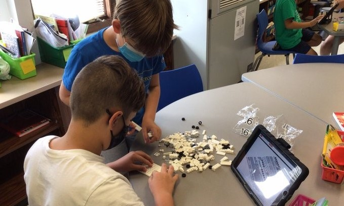 Two students building a lego set while following directions from the iPad