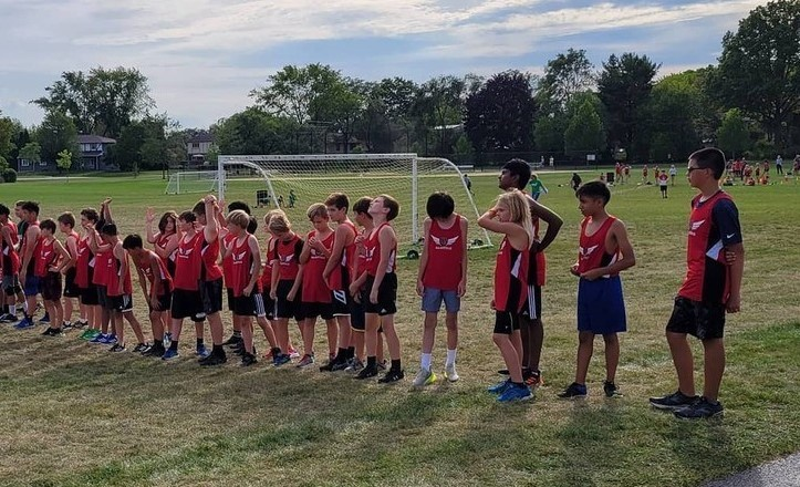 Cross country runners lined up on the field ready to run